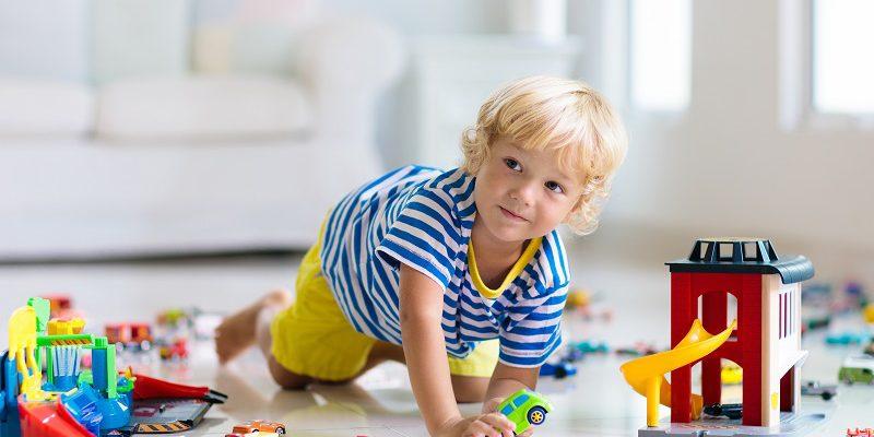 Mały chłopiec bawiący się na podłodze samochodzikami
